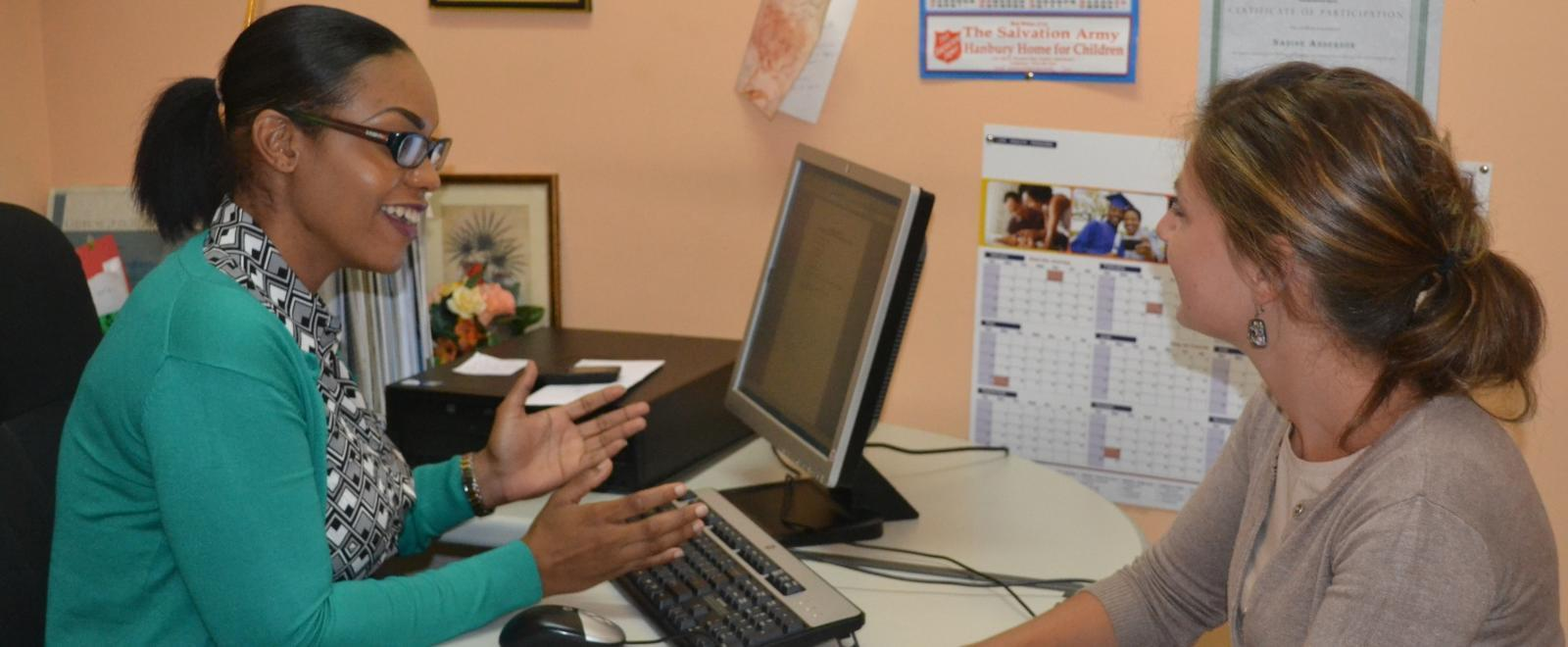 Trabajadora social discute un caso con una pasante.